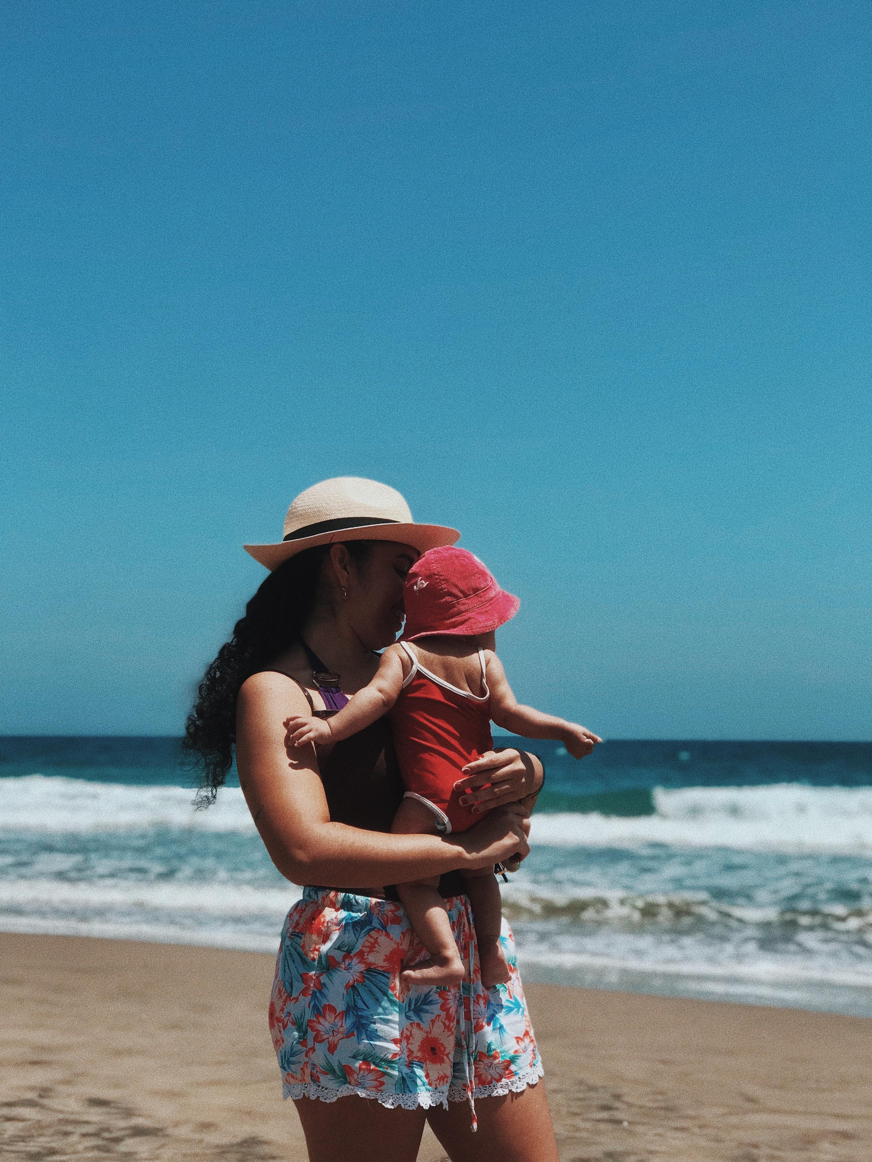 mama con bebe en playa crema de sol protector